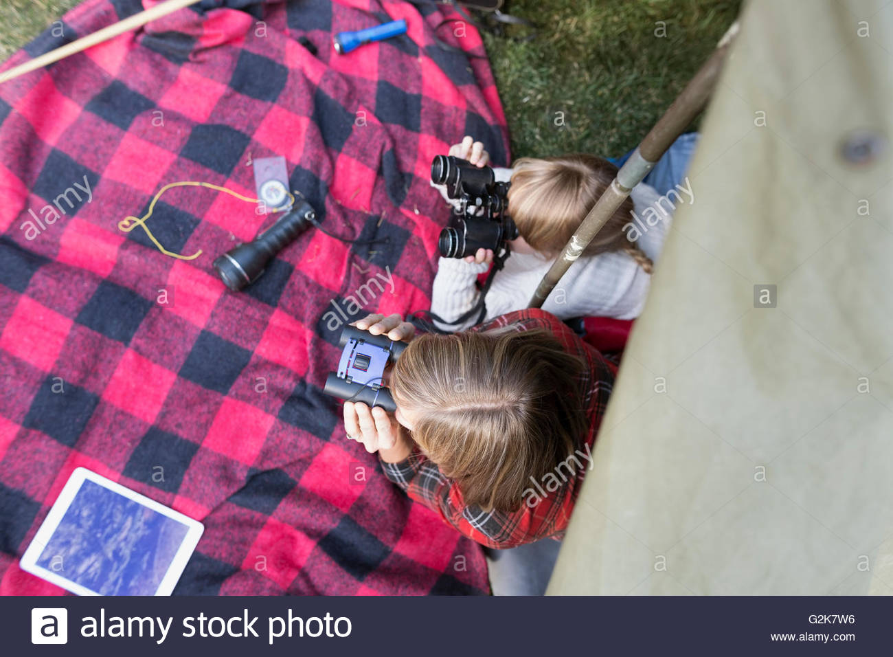 Overhead view sisters using binoculars in tent - Stock Image