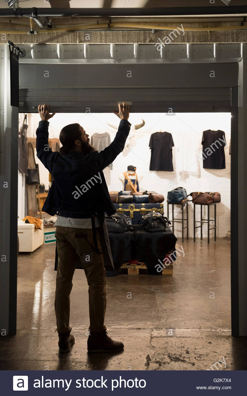 Leather shop owner entrepreneur opening shop gate - Stock Image