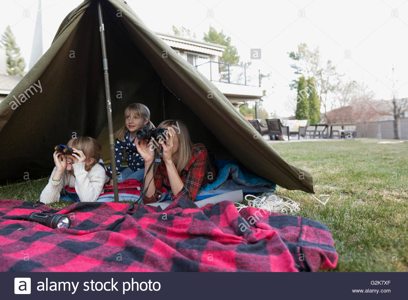 Mother and daughters using binoculars in backyard tent - Stock Image