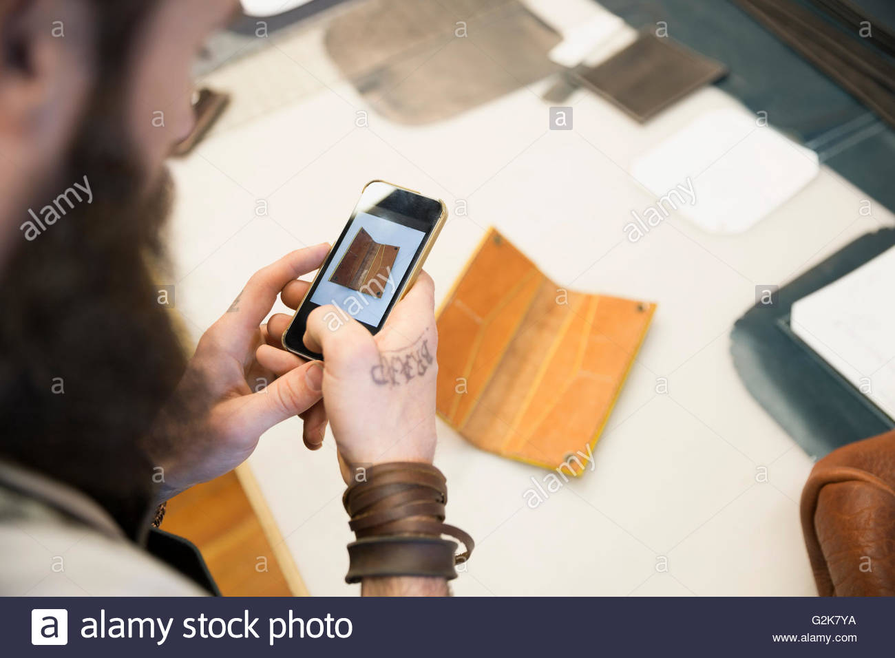 Leather worker photographing leather with camera phone - Stock Image