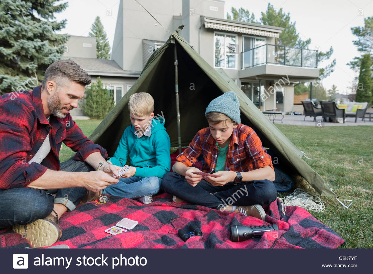 Father and sons playing cards at backyard tent - Stock Image