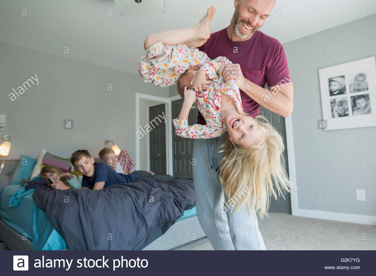 Playful father tickling daughter upside-down in bedroom - Stock Image