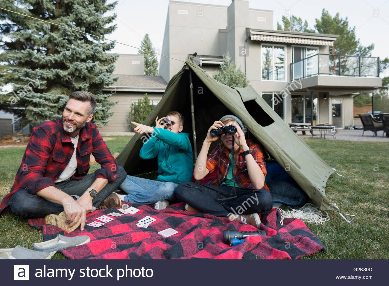 Father and sons with binoculars in backyard tent - Stock Image