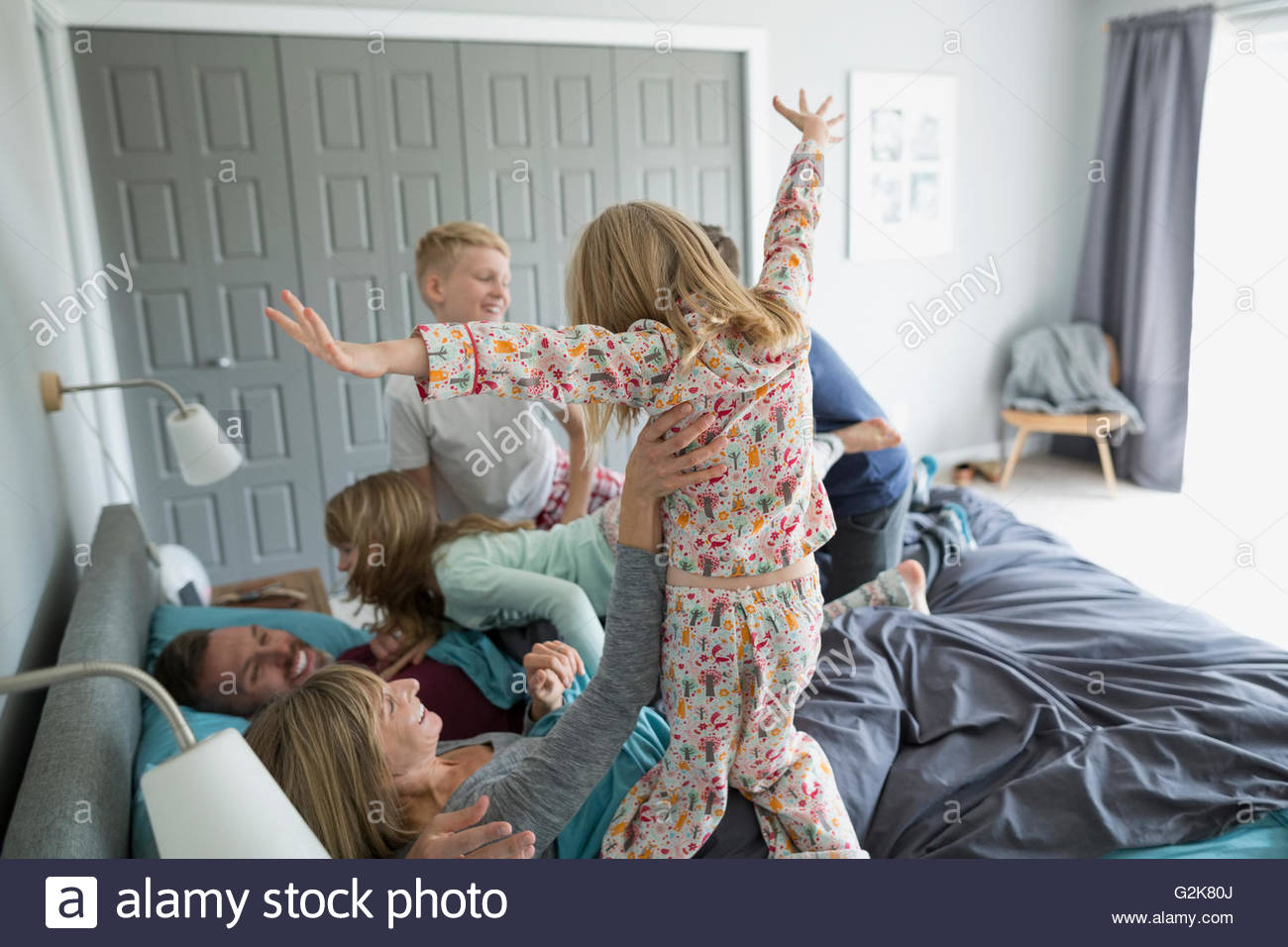 Playful children in pajamas jumping on parents in bed - Stock Image