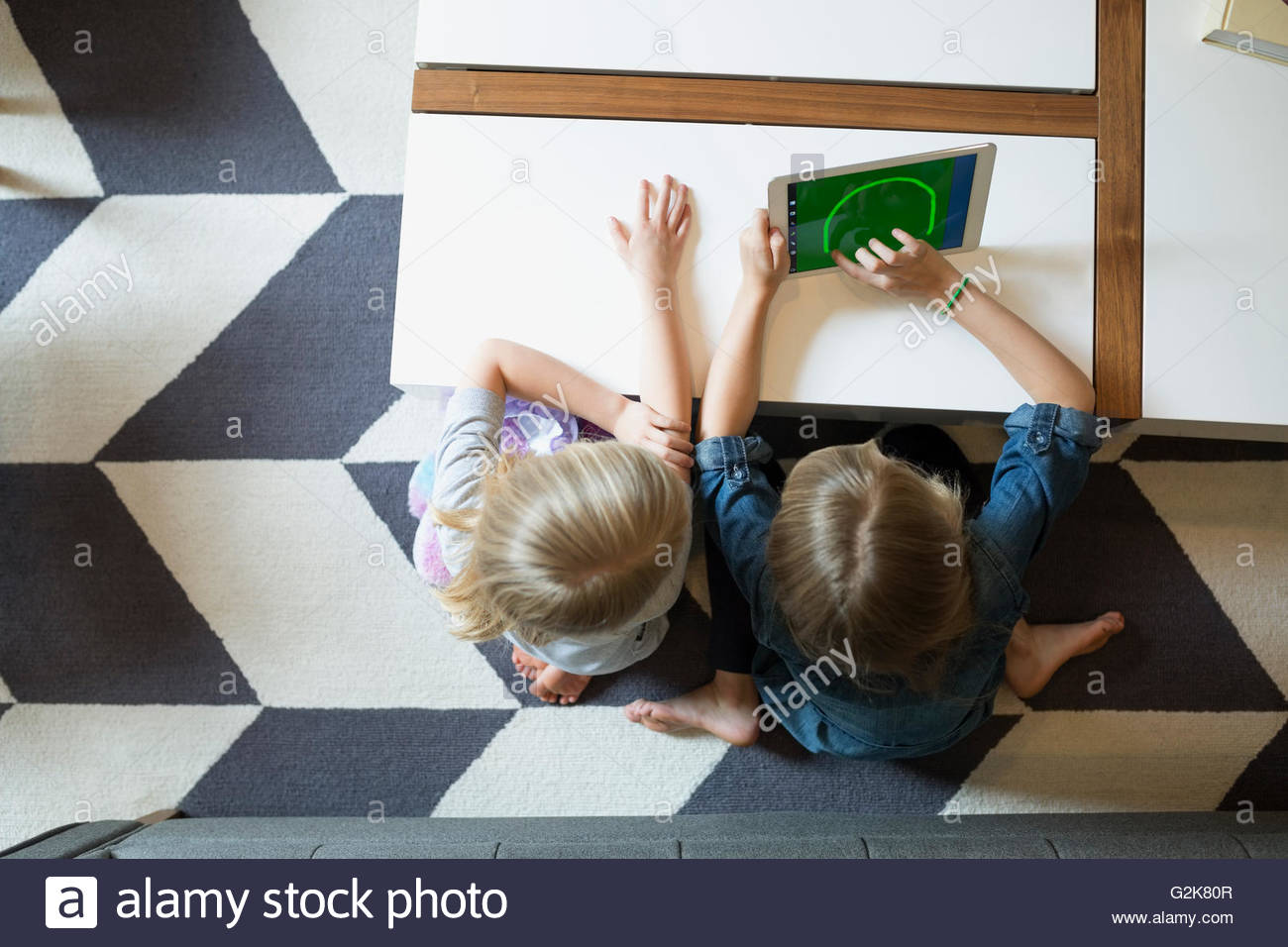 Overhead view of sisters using digital tablet - Stock Image