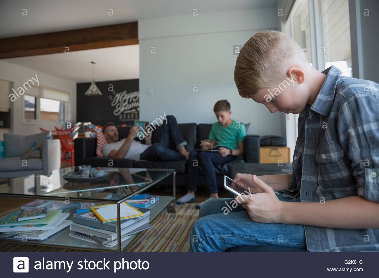 Father and sons relaxing with digital tablets in living room - Stock Image