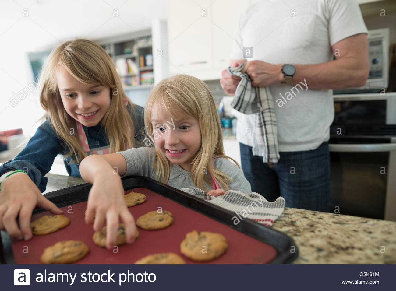 Excited girls reaching for fresh baked cookies in kitchen - Stock Image