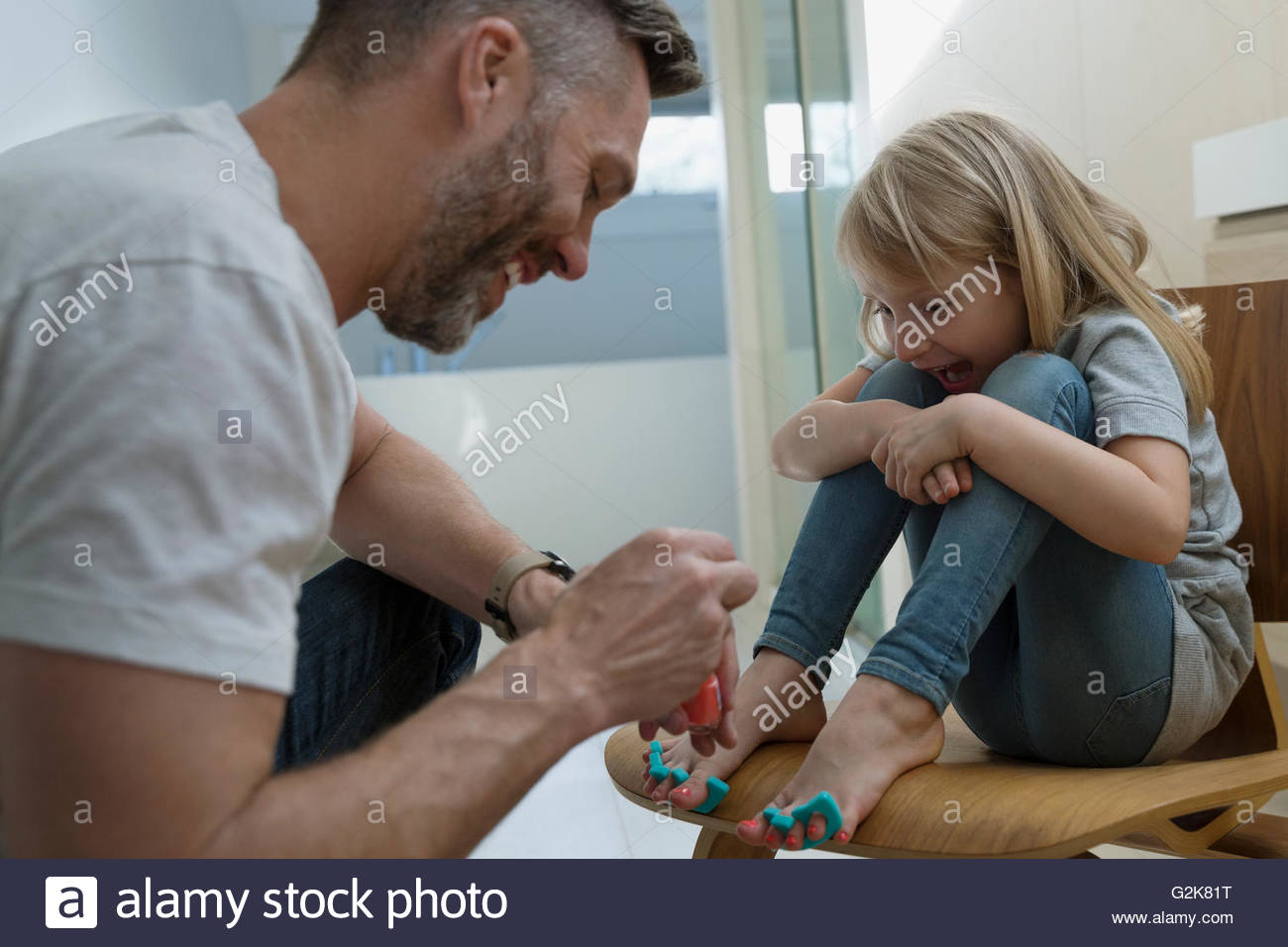 Father painting daughters toenails with nail polish - Stock Image