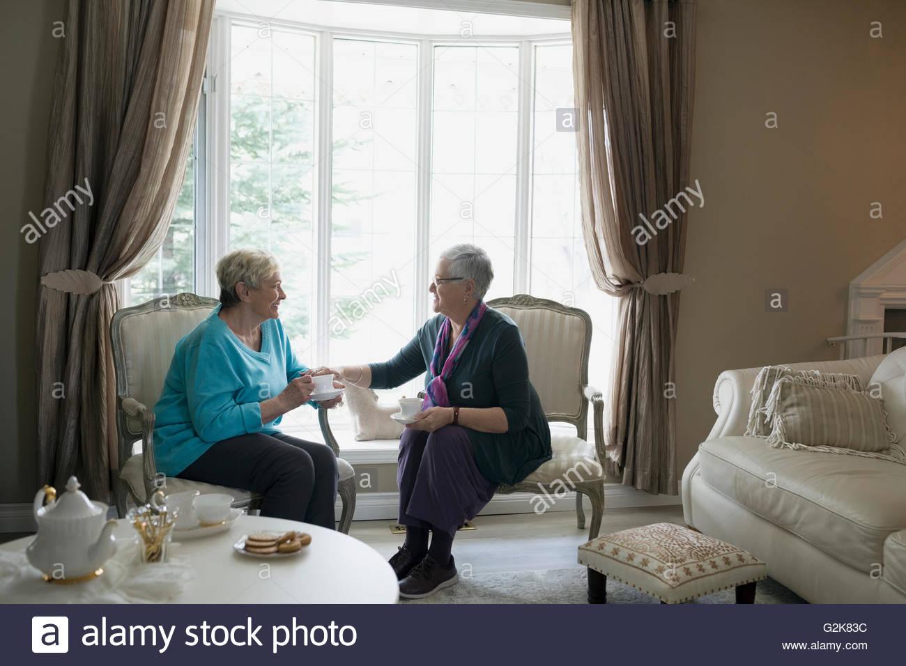 Senior women drinking tea and talking in living room - Stock Image