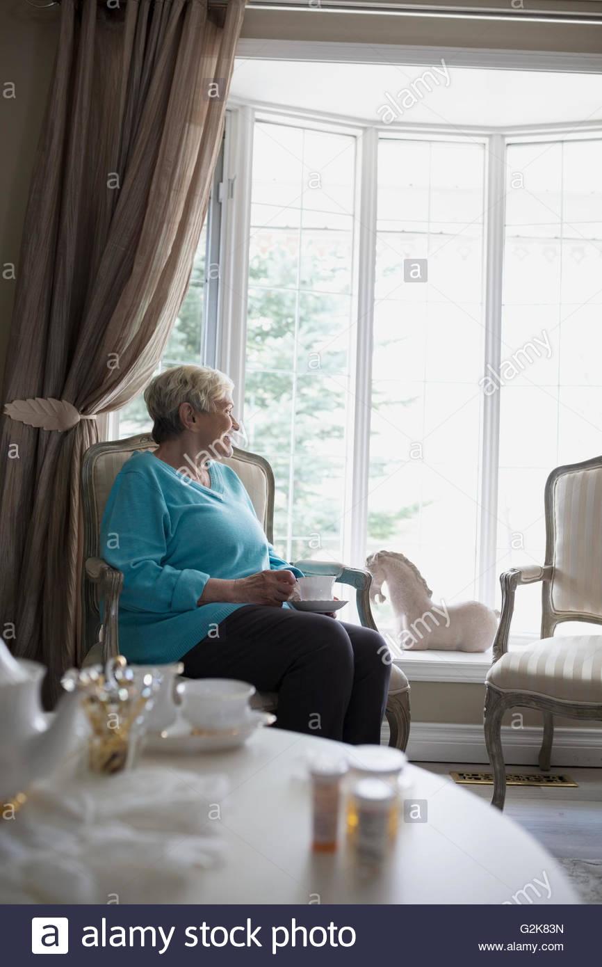 Senior woman drinking tea looking through window Stock Photo