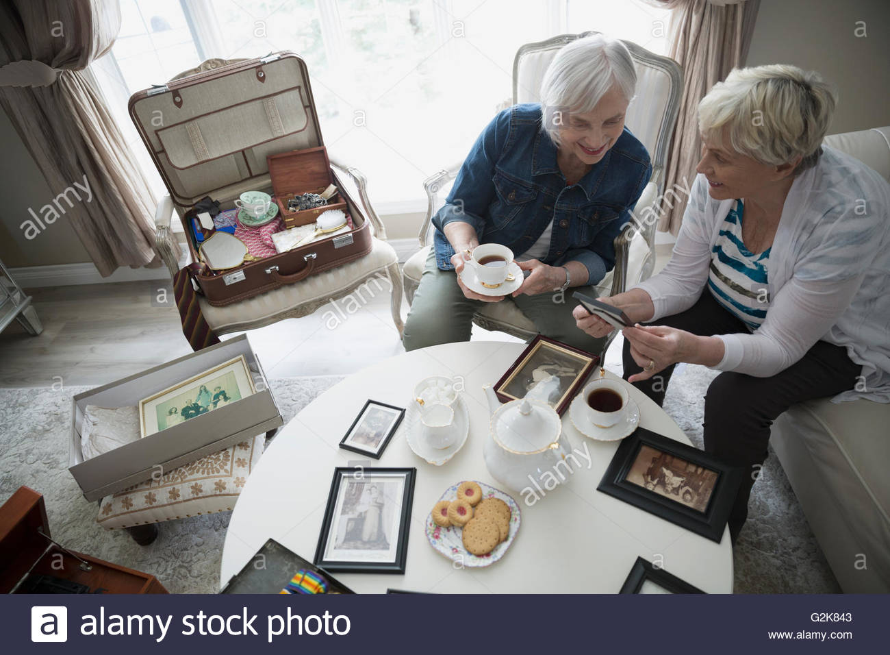 Senior women drinking tea and looking at old photographs - Stock Image