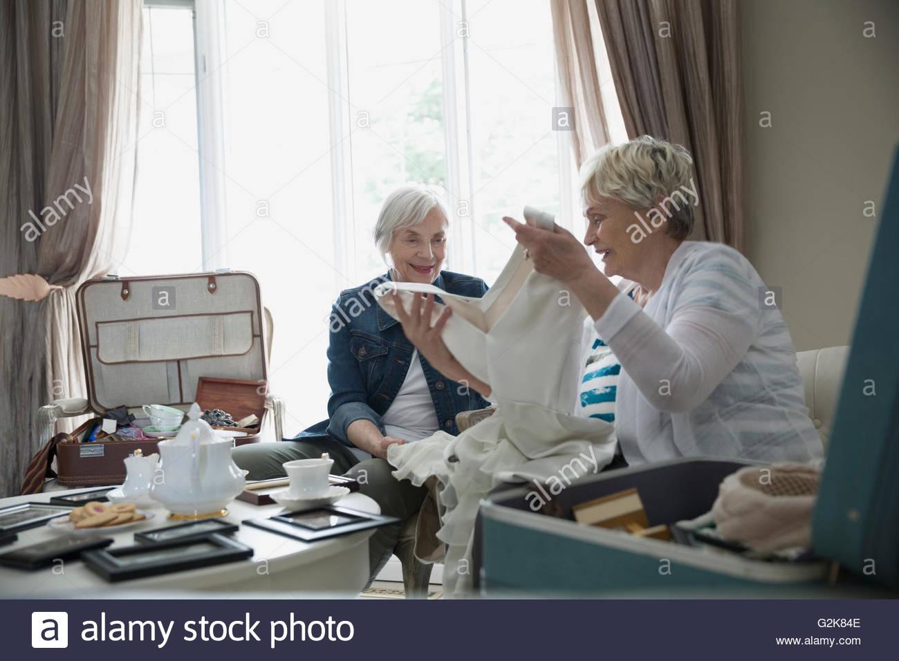 Senior women drinking tea and looking at old wedding dress - Stock Image