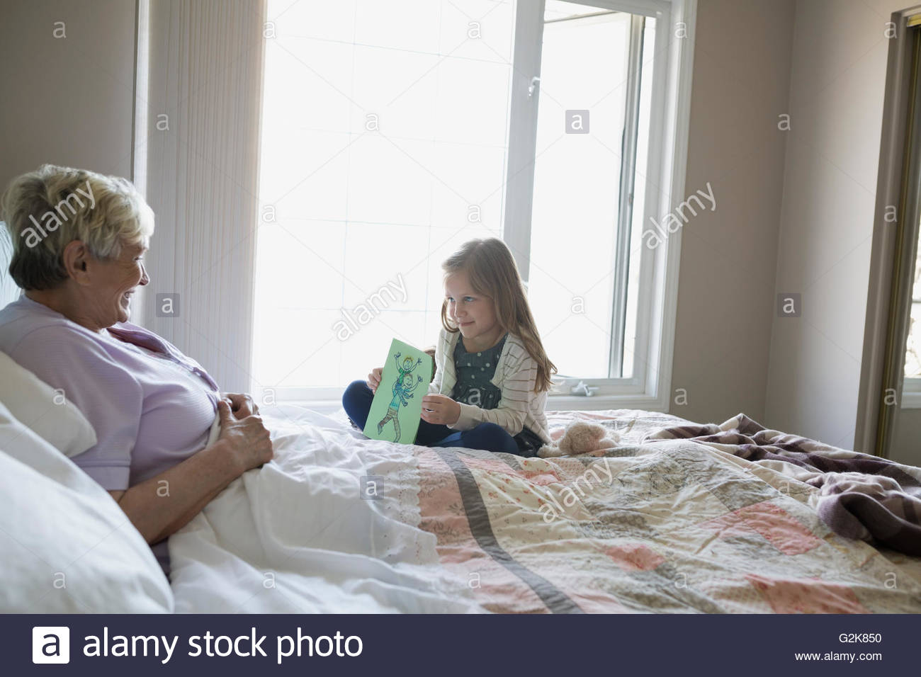 Granddaughter showing handmade drawing to grandmother in bed Stock Photo