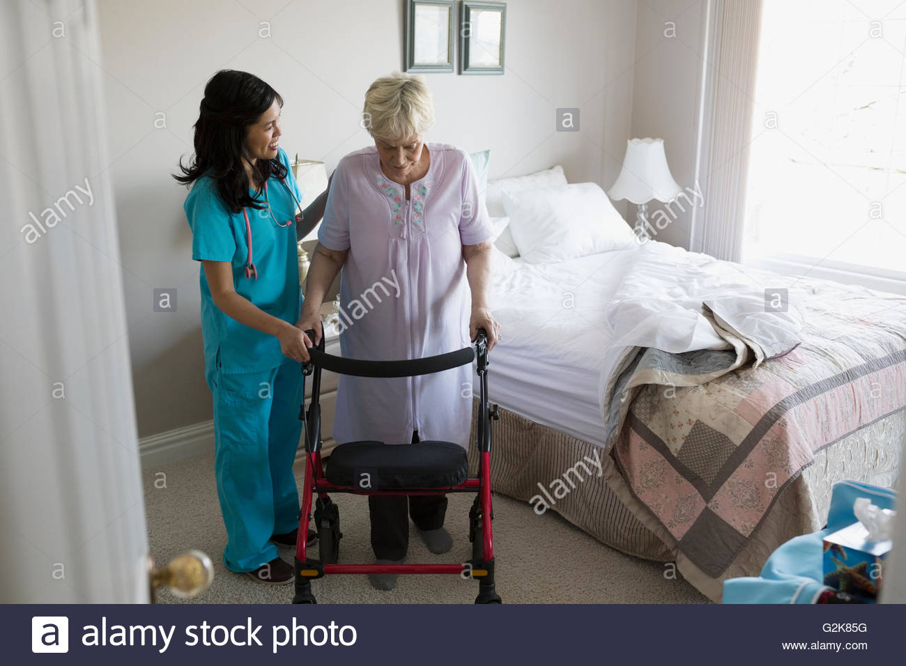 Home caregiver helping senior woman with walker in bedroom - Stock Image