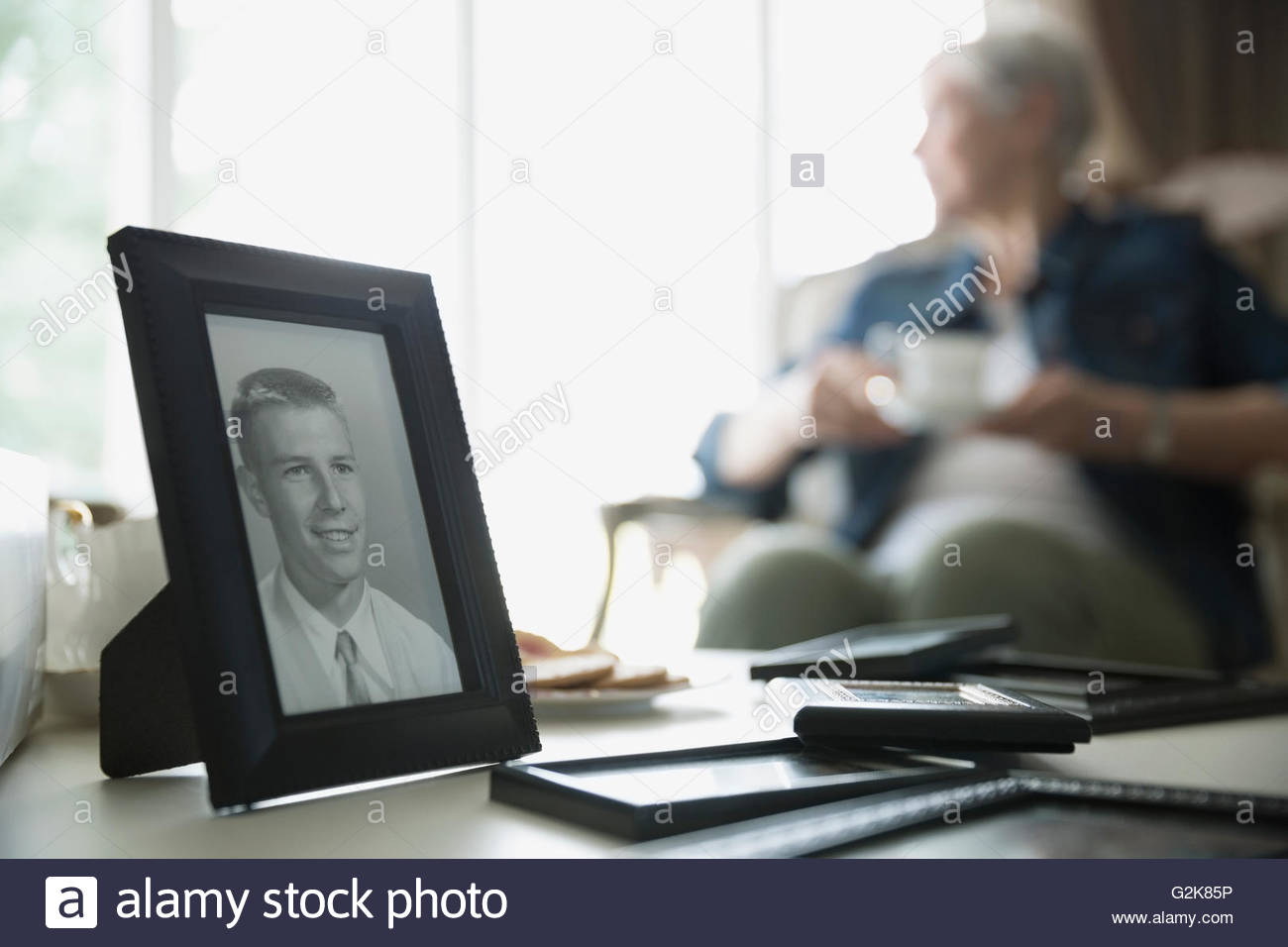 Old photograph of man with senior woman in background - Stock Image