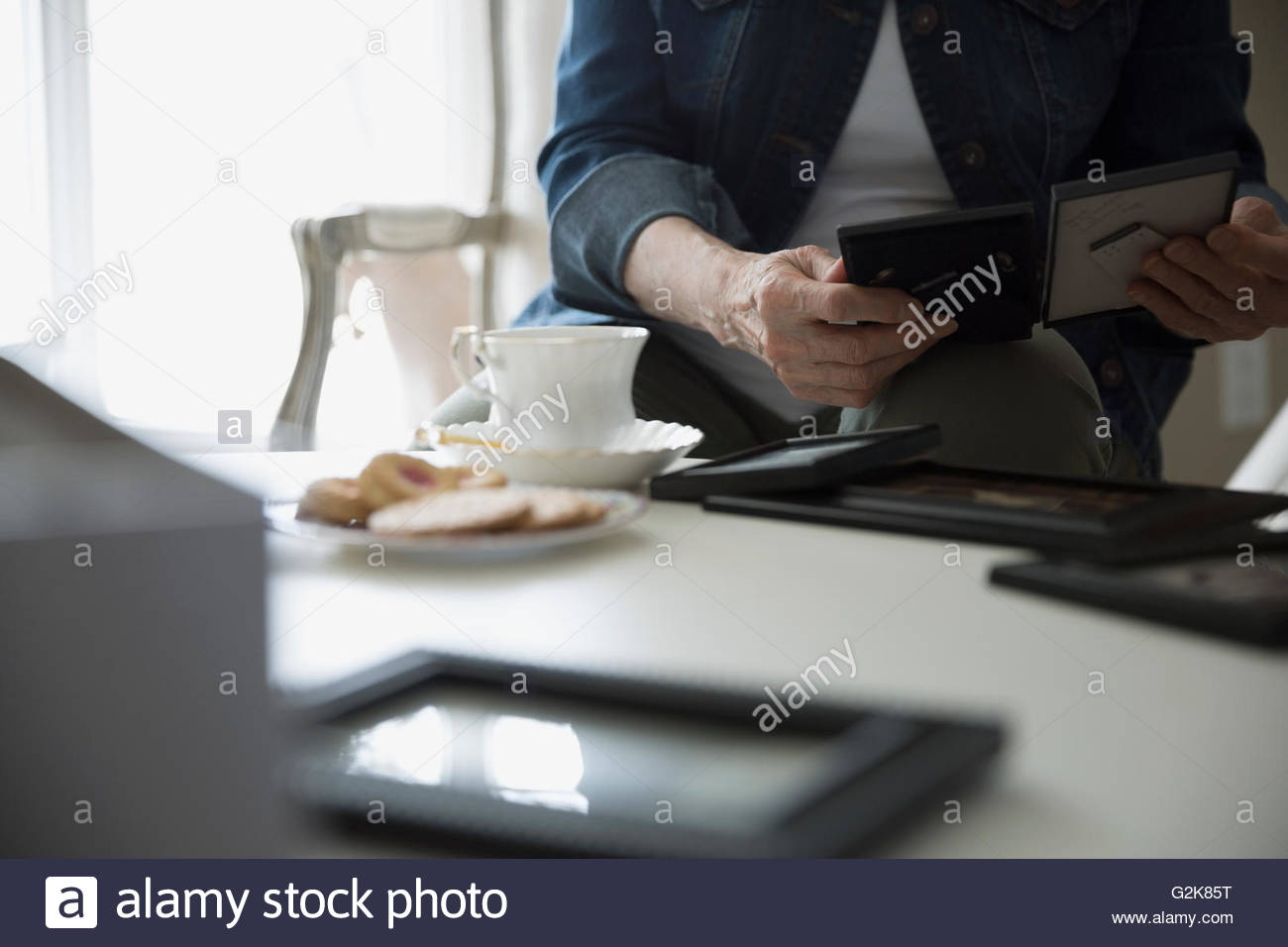 Senior woman drinking tea and looking at old photographs - Stock Image