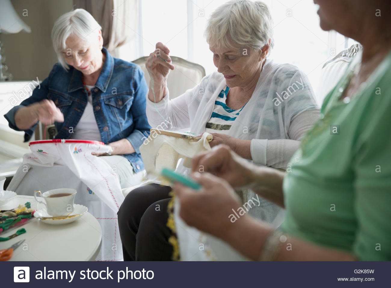 Senior women drinking tea and embroidering - Stock Image