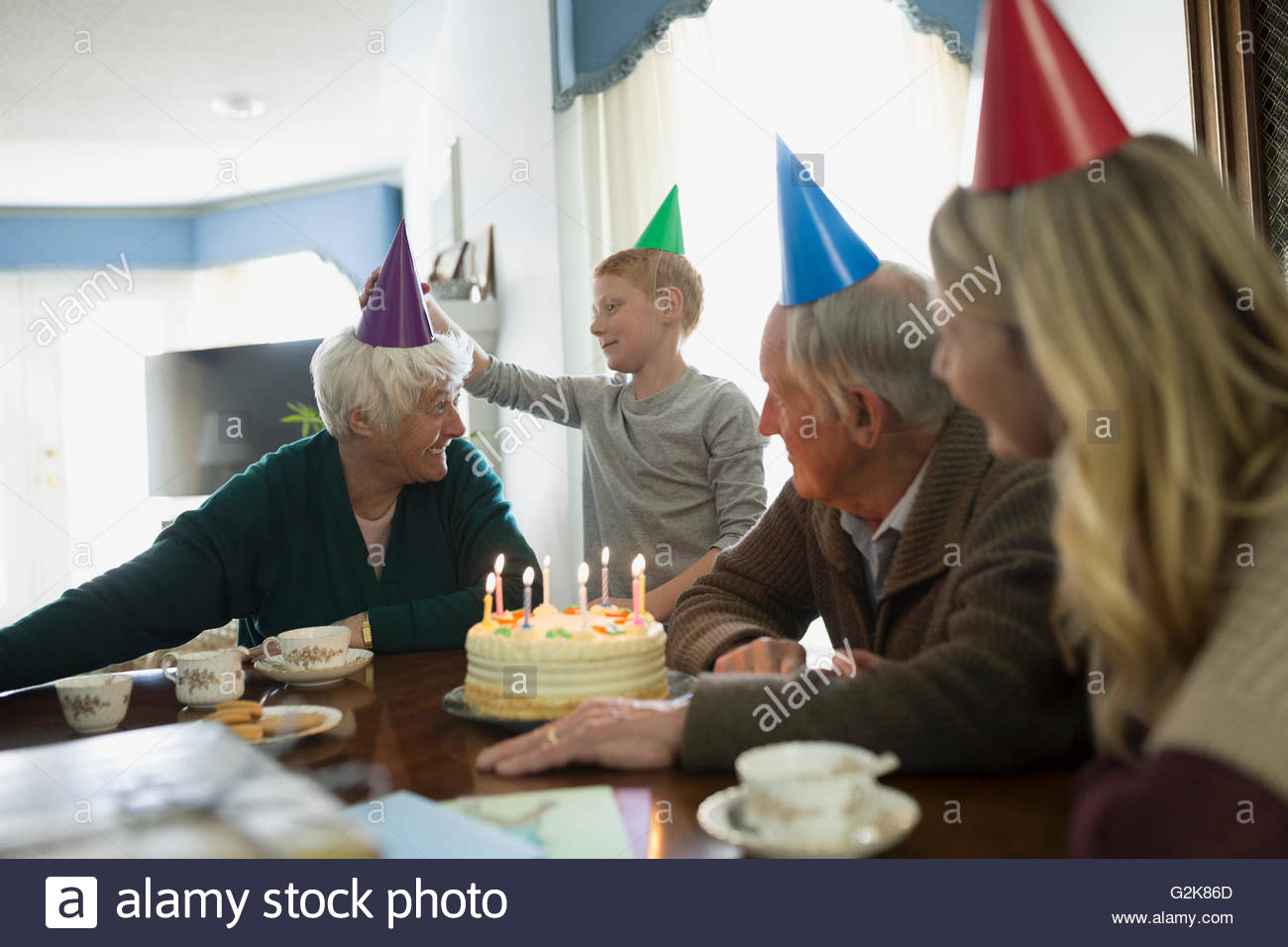 Multi Generation Family Celebrating Birthday With Cake And Party Hats