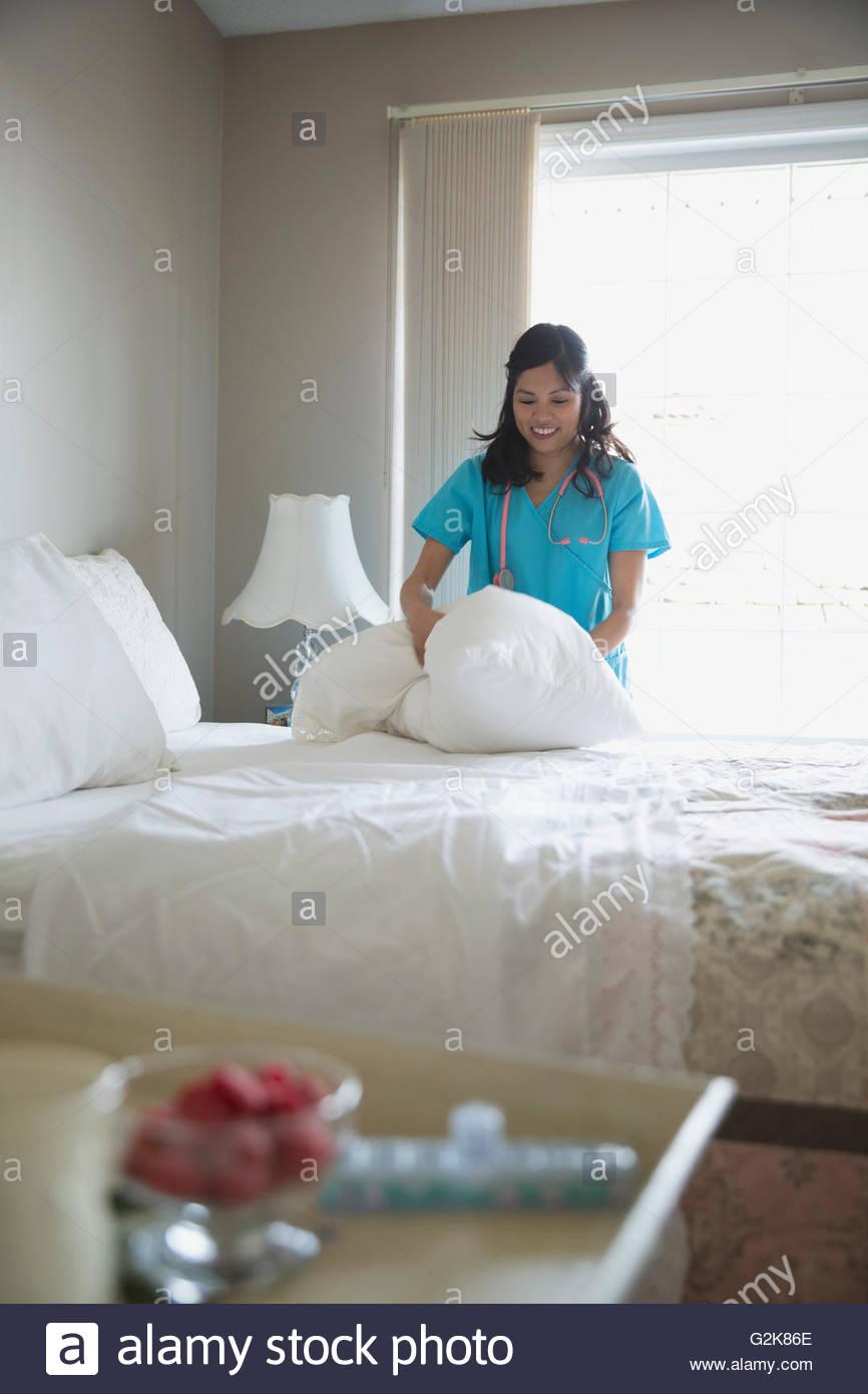 Smiling home caregiver making bed - Stock Image