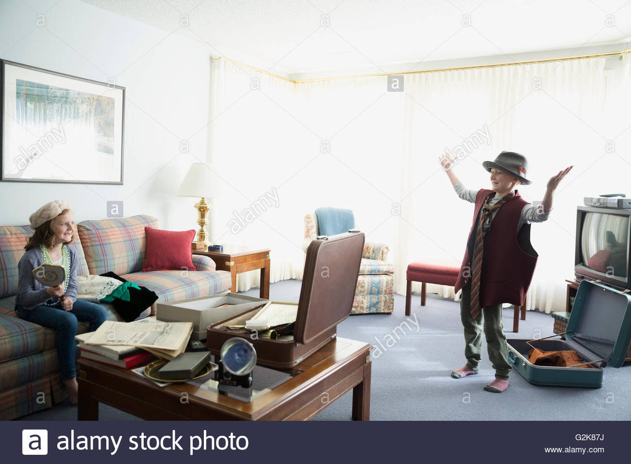 Brother and sister playing with old memorabilia in living room - Stock Image