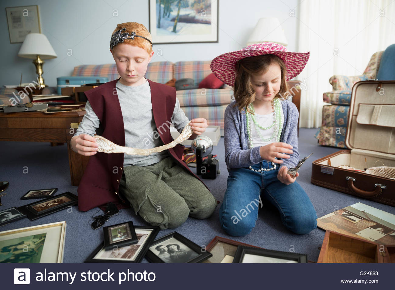 Brother and sister going through old memorabilia - Stock Image