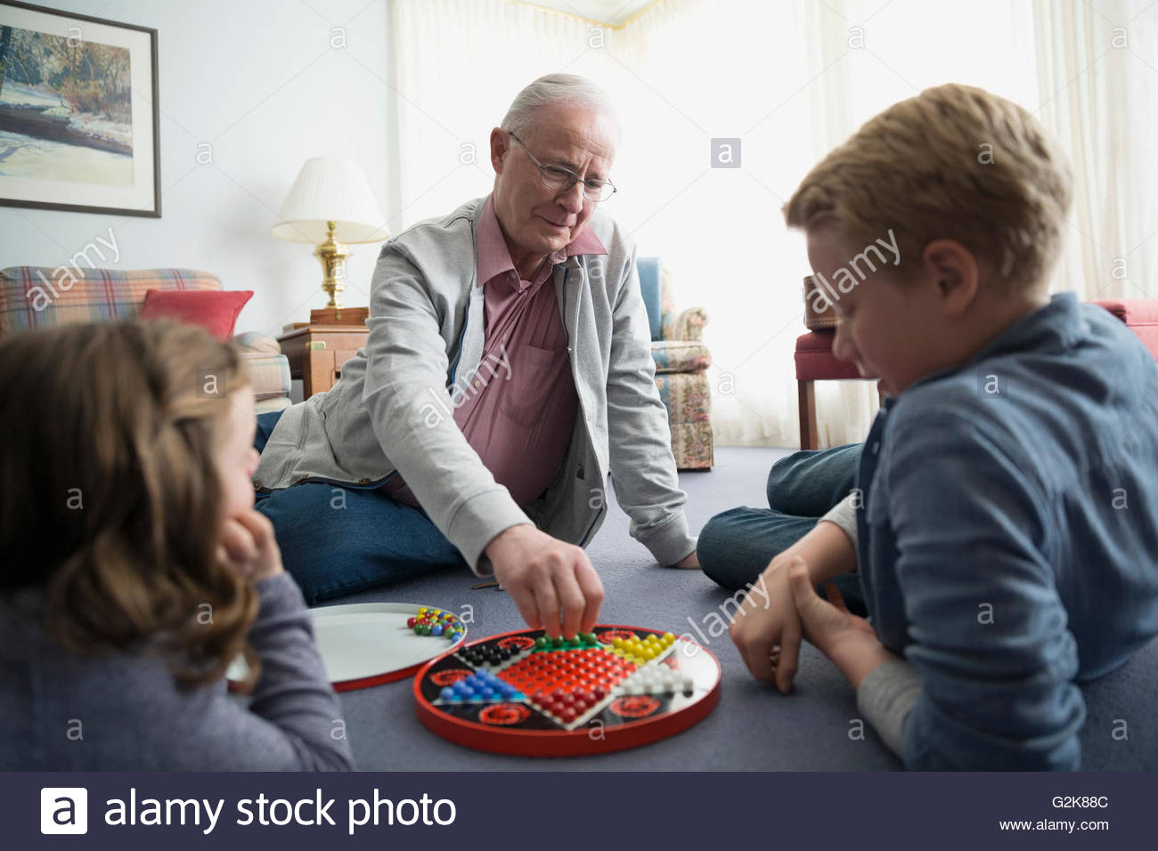 Grandfather and grandchildren playing Chinese checkers - Stock Image
