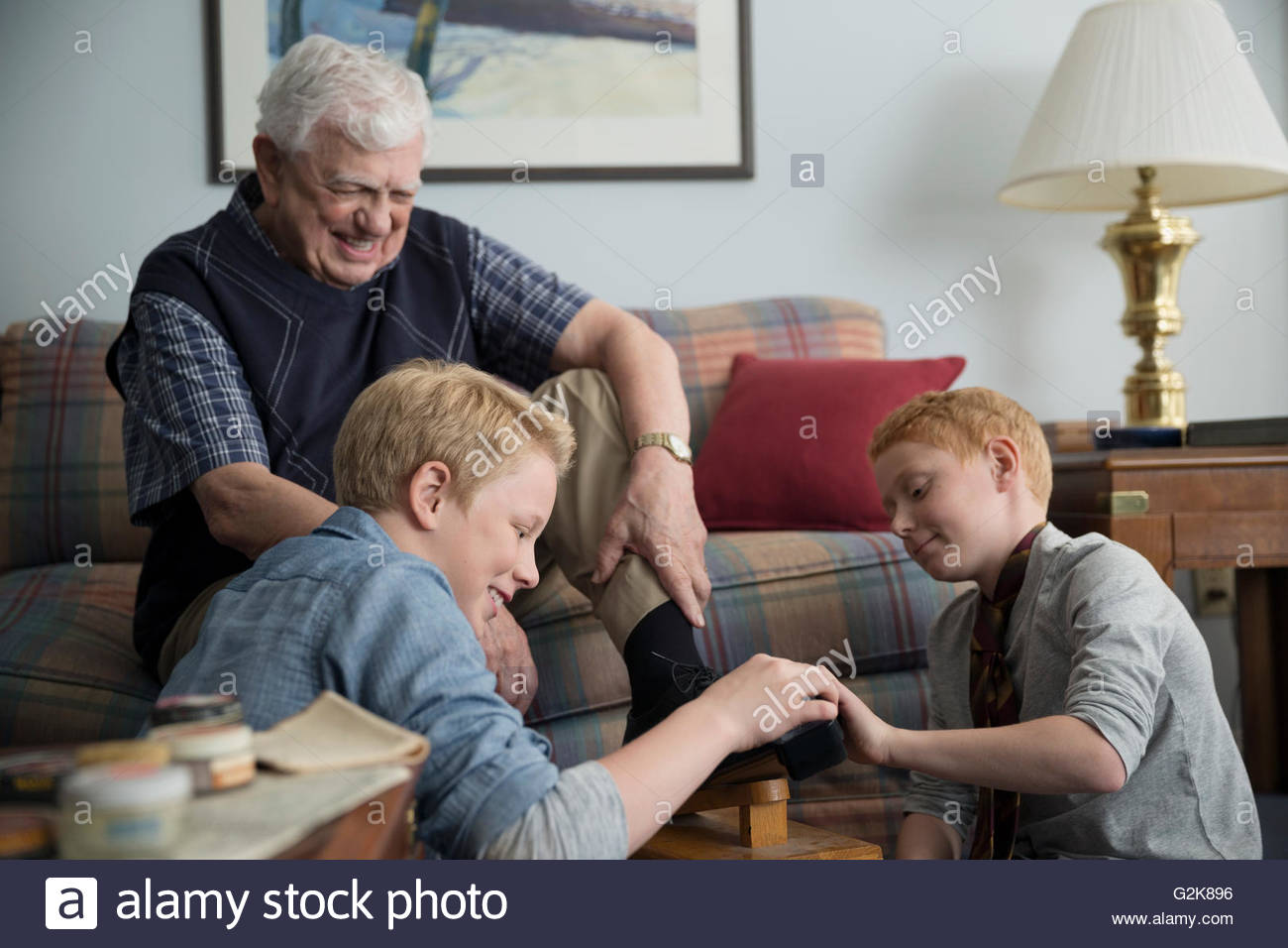 Grandsons polishing shoes for grandfather in living room - Stock Image