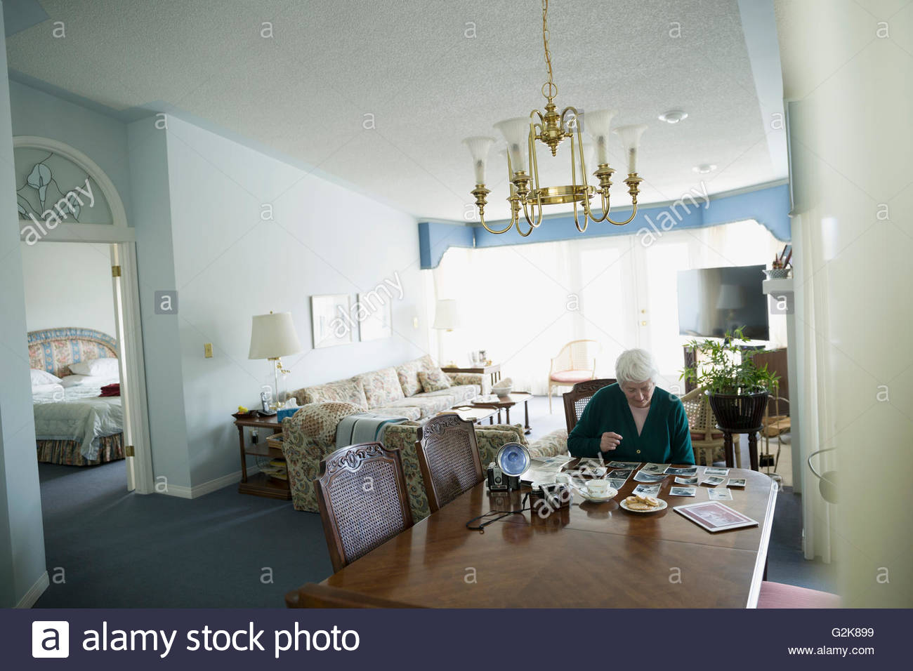 Senior woman looking at old photographs at dining room table - Stock Image