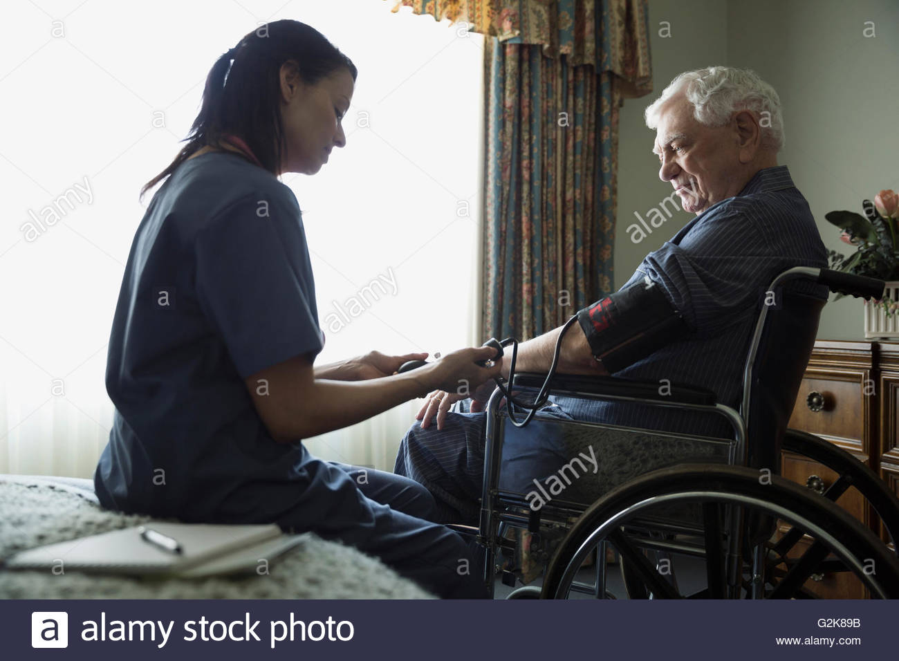 Home caregiver checking blood pressure for senior man in wheelchair - Stock Image