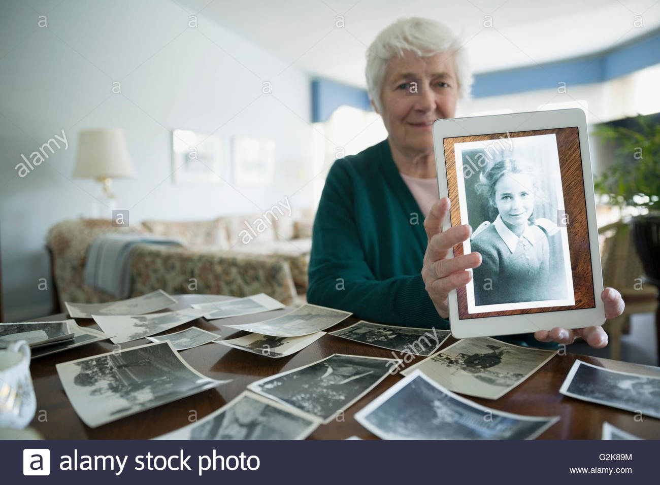 Portrait smiling senior women holding digital tablet with old photograph of younger self - Stock Image