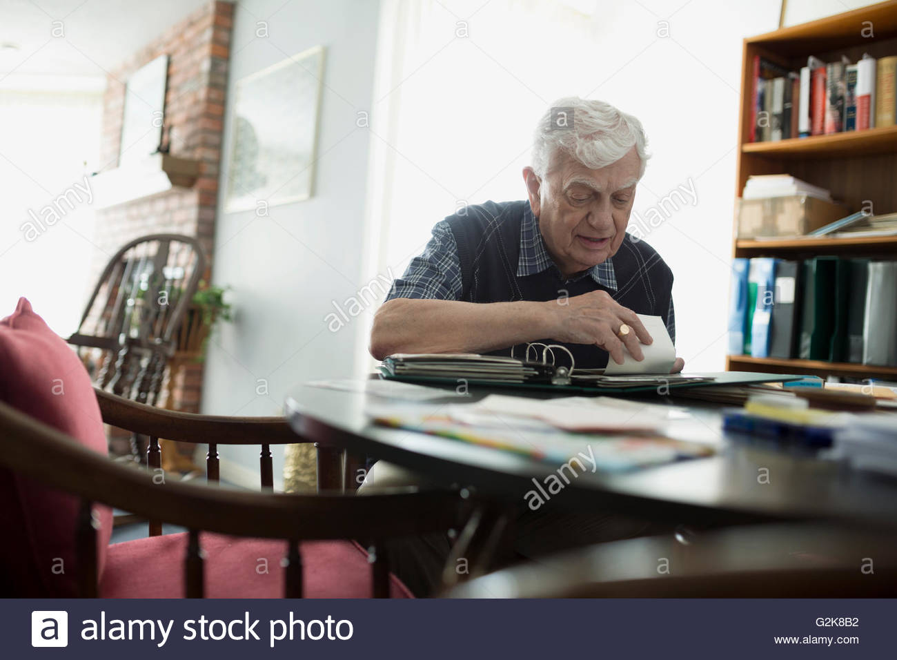 Senior man looking through photograph album - Stock Image