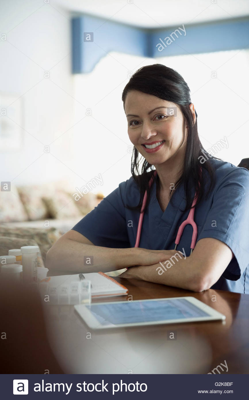 Portrait confident home caregiver with digital tablet and prescription bottles - Stock Image