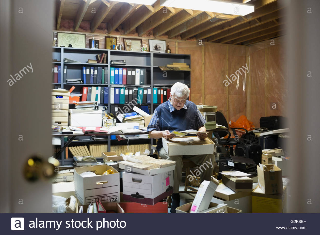 Senior man reading old letters in boxes - Stock Image
