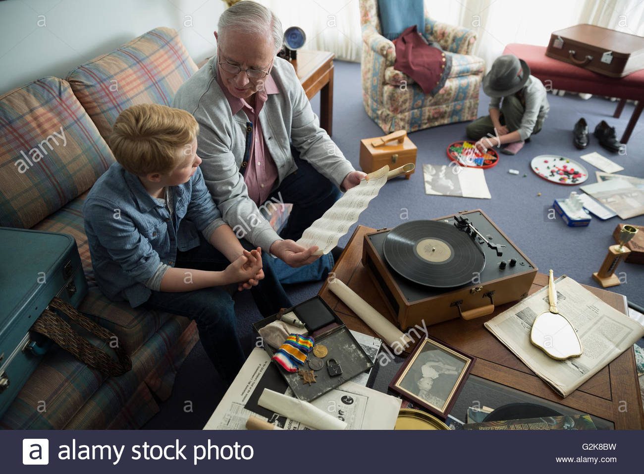 Grandfather and grandson looking through old memorabilia - Stock Image