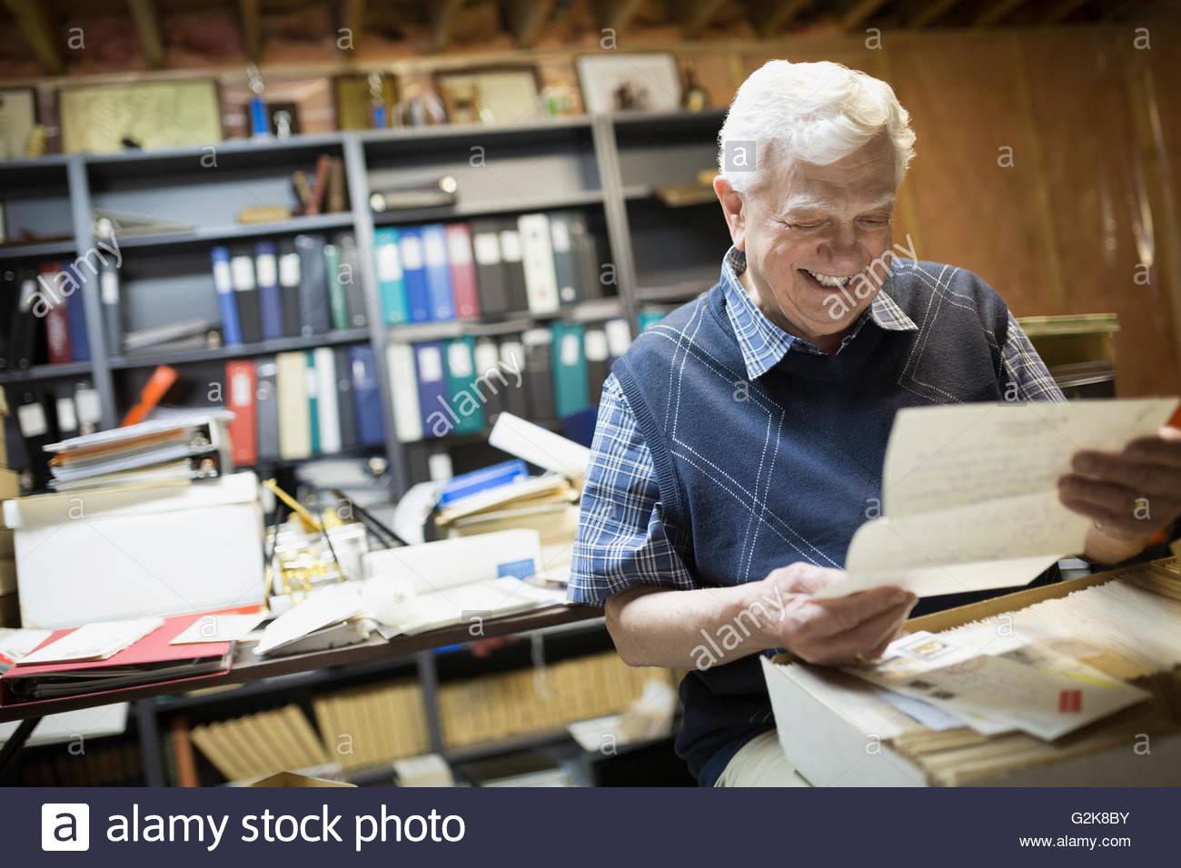Smiling senior man reading old letters - Stock Image