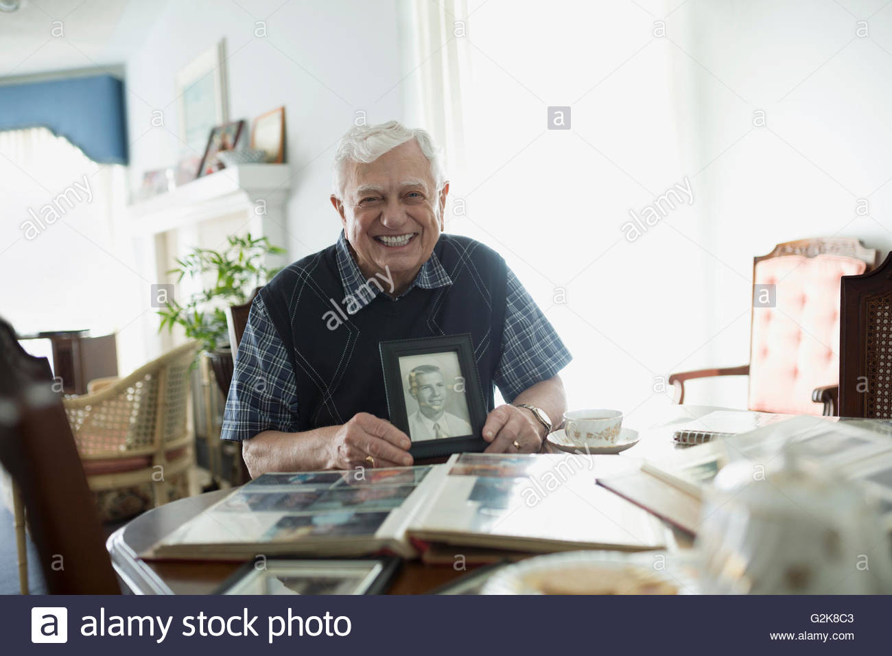 Portrait smiling senior man holding old photograph of his younger self - Stock Image