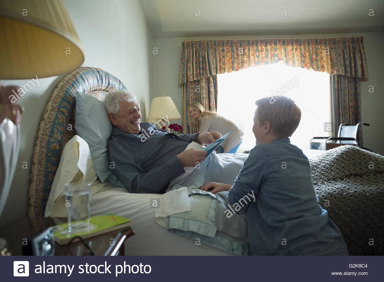 Grandson visiting grandfather resting in bed - Stock Image