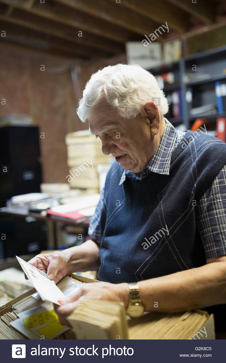 Senior man going through belongings in boxes - Stock Image