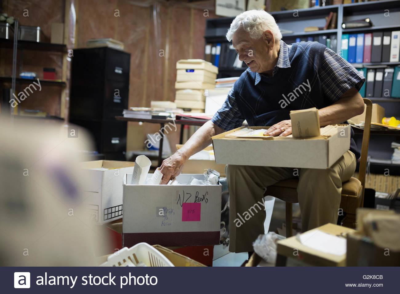 Senior man going through belongings in boxes - Stock Image