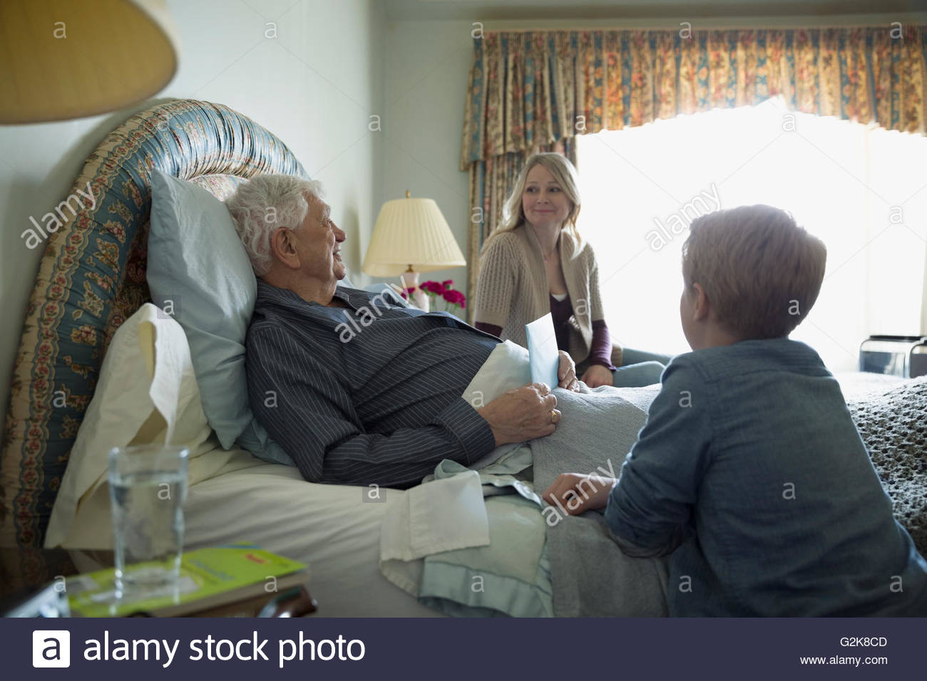 Daughter and grandson visiting grandfather resting in bed - Stock Image
