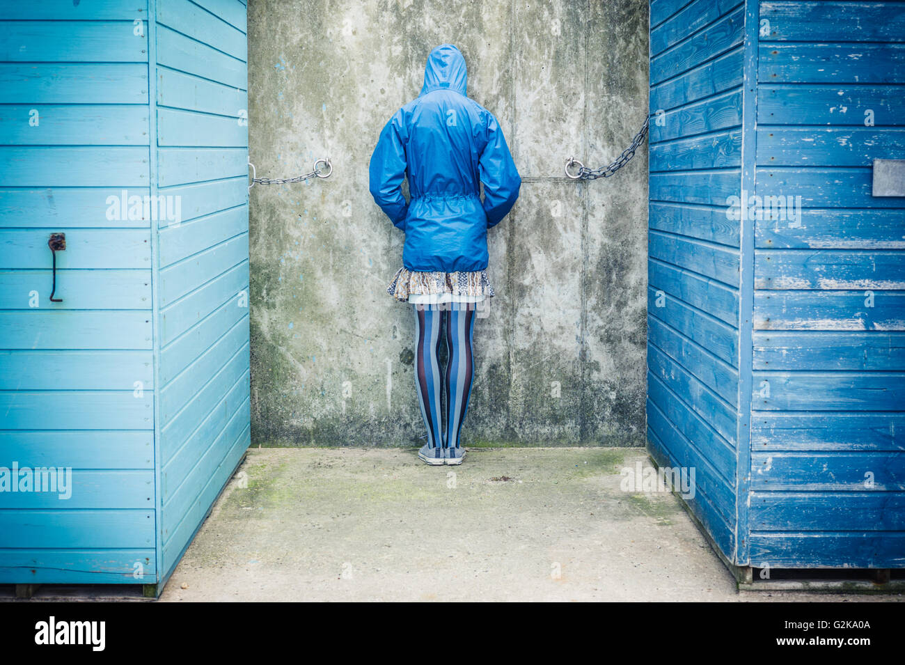 A person is standing with their head against the wall in between two beach huts Stock Photo