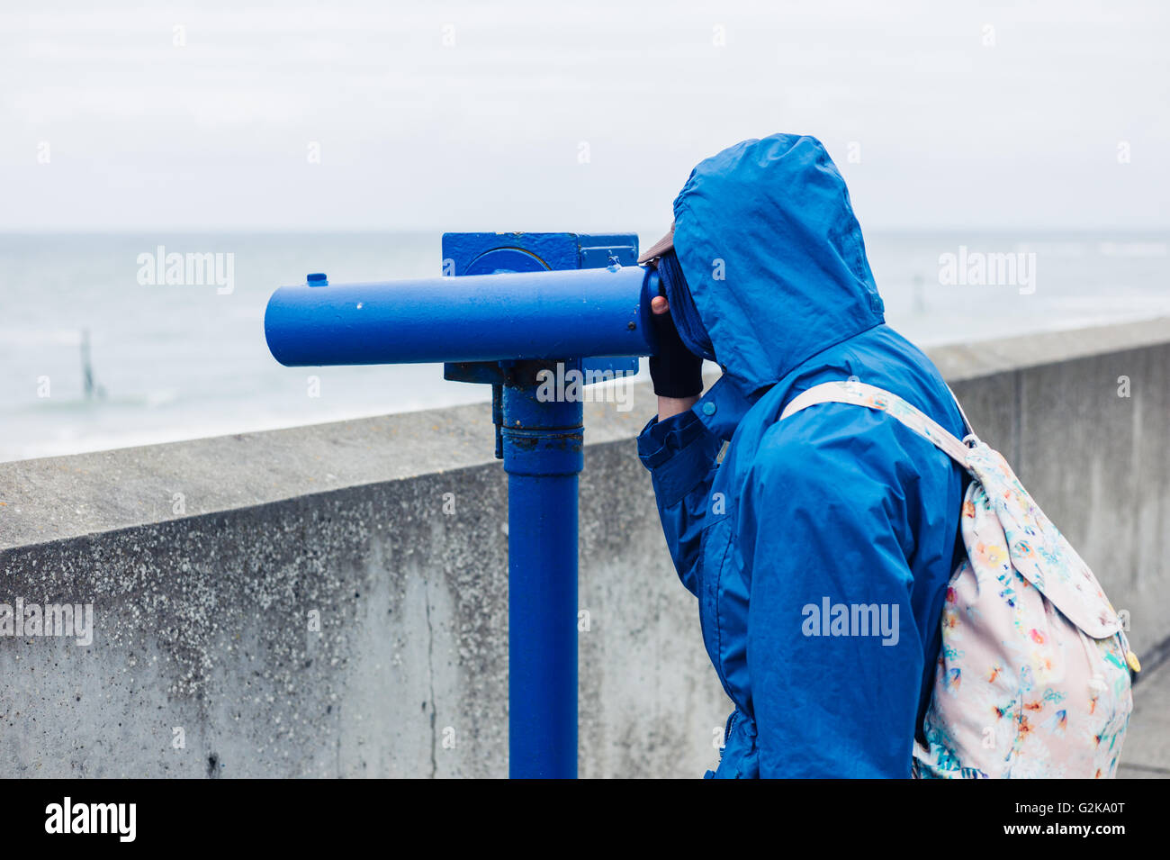A person wearing a blue jacket and hood is using a telescope on the coast - Stock Image