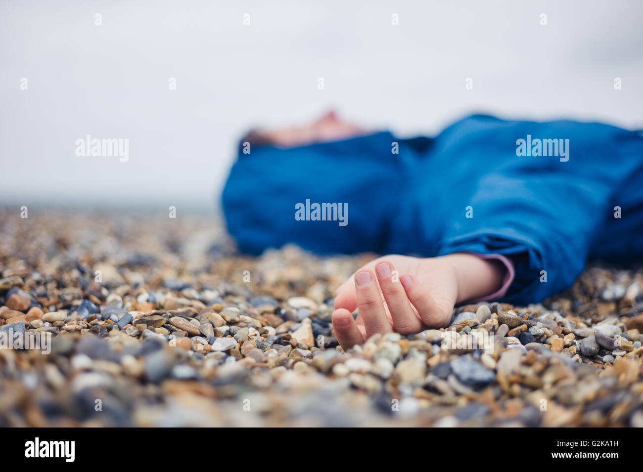 An unconscious woman is lying on a shingle beach - Stock Image
