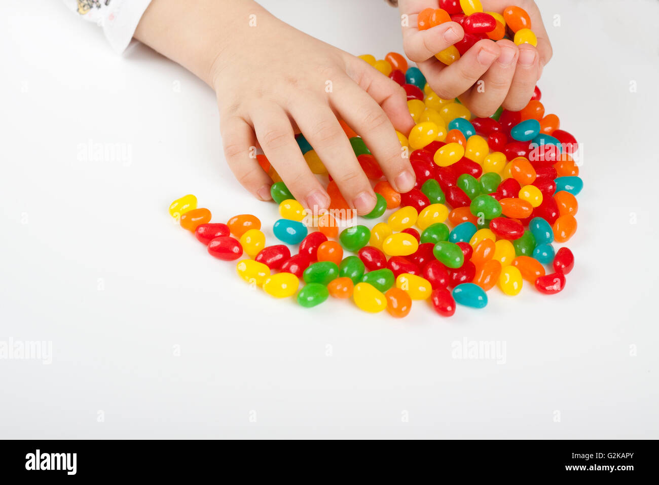 child grabing and holding lot's of colored candy Stock Photo