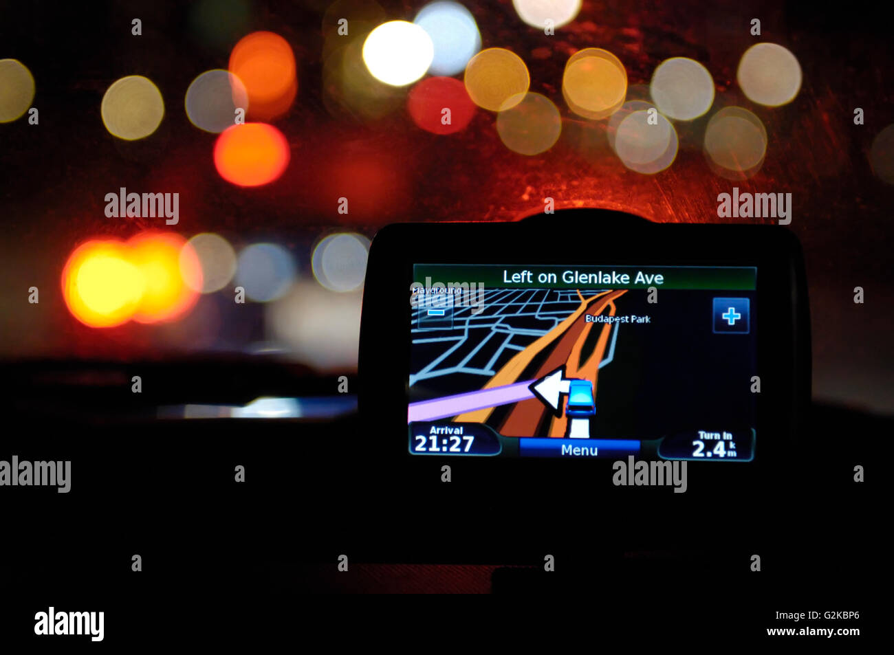 GPS navigational device on a windshield of a car at night - Stock Image