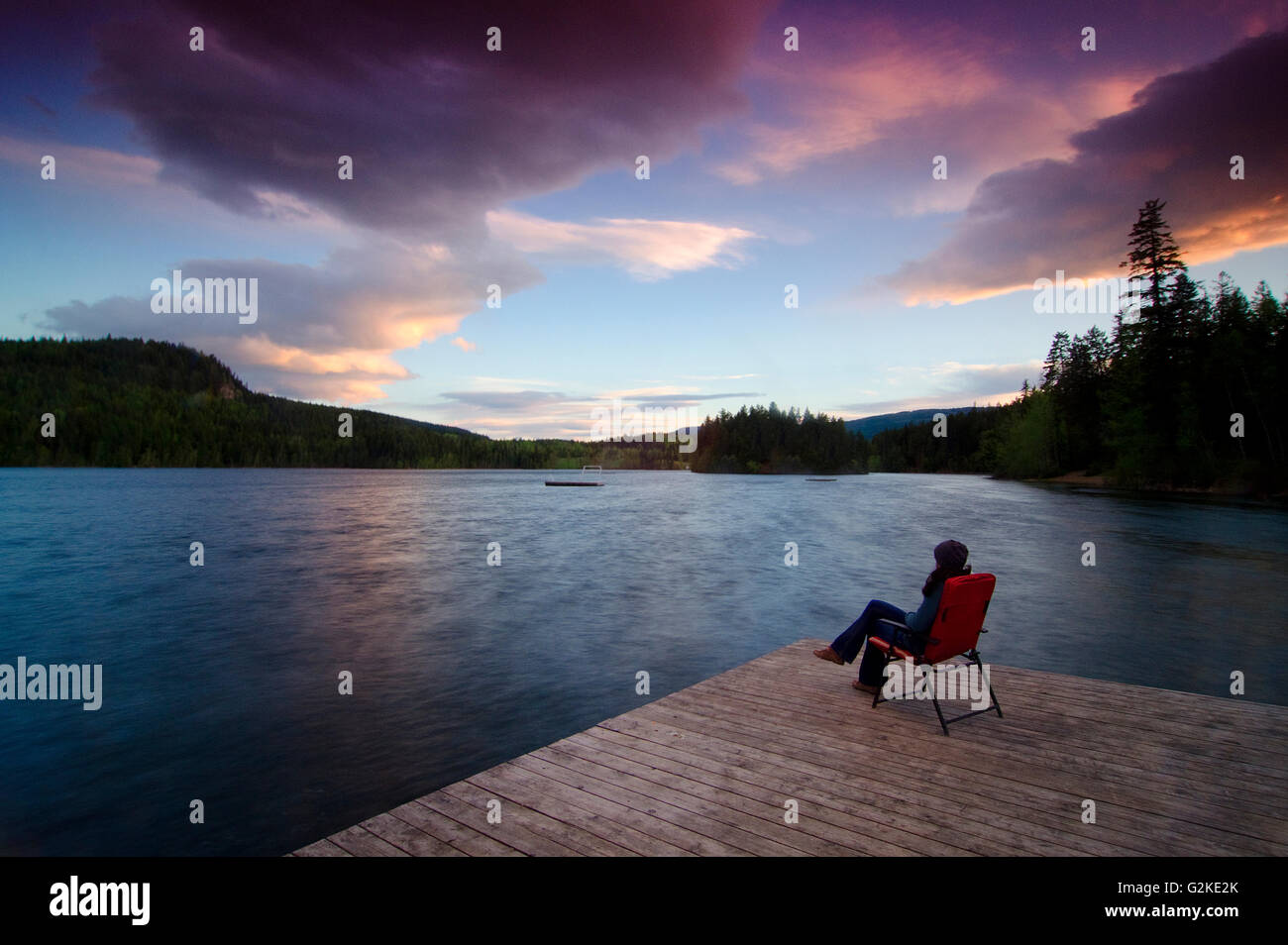 Woman relaxes and watches the sunset from the wharf at Gardom Lake near Salmon Arm, British Columbia, Canada, MR022 - Stock Image