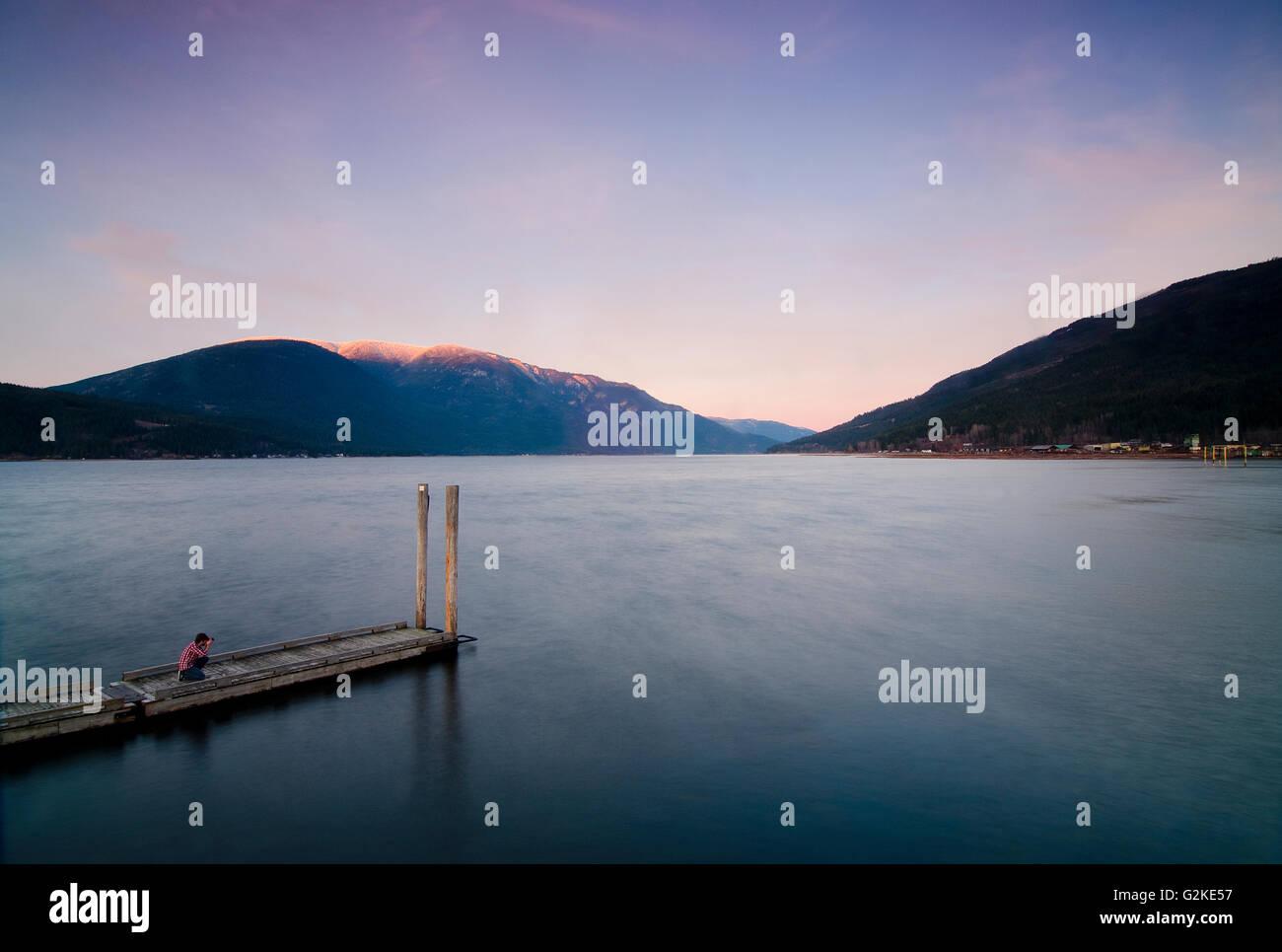 Photographer shoots on public access wharf on Shuswap Lake sunset near Salmon Arm in Shuswap region British Columbia - Stock Image