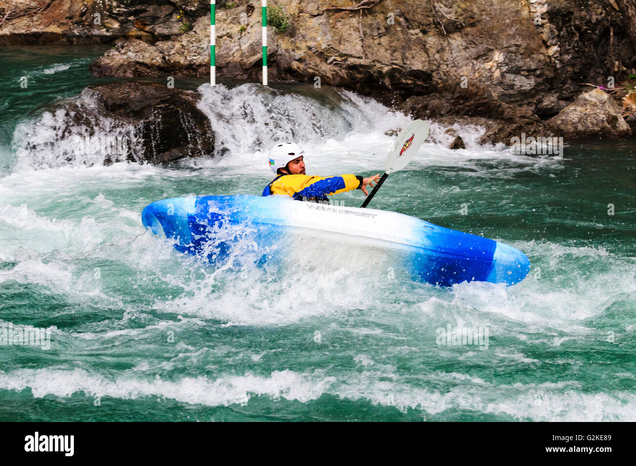 A slalom kayaker tries to stabilize his kayak while navigating the Kananaskis River at the Canoe Meadows course - Stock Image
