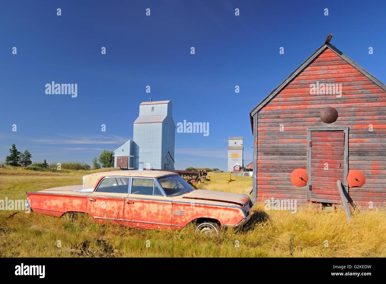 Old car, grain elevator and sheds Darcy Saskatchewan Canada - Stock Image