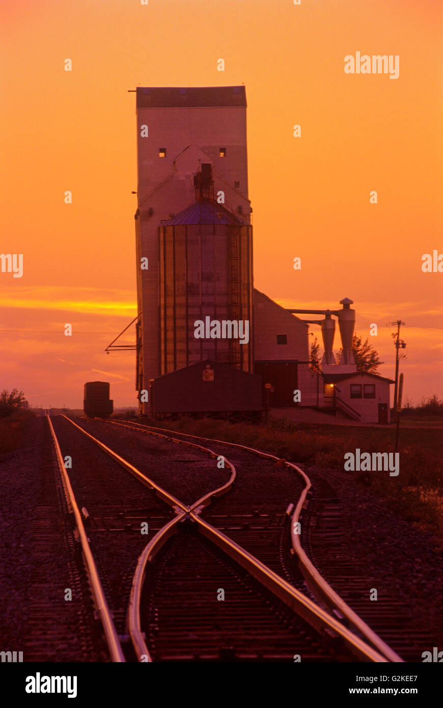 Grain elevator and rail tracks silhouetted against a sunset sky Wolseley Saskatchewan Canada - Stock Image